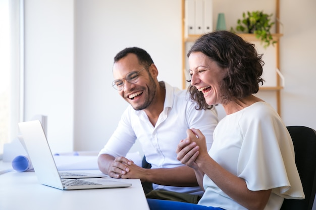 Cheerful employees looking at laptop and laughing Free Photo
