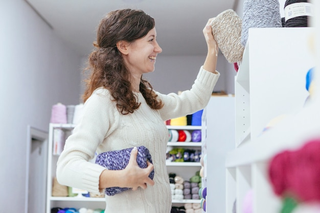 Cheerful enterprising young woman organizing wool yarns at her own art business Premium Photo