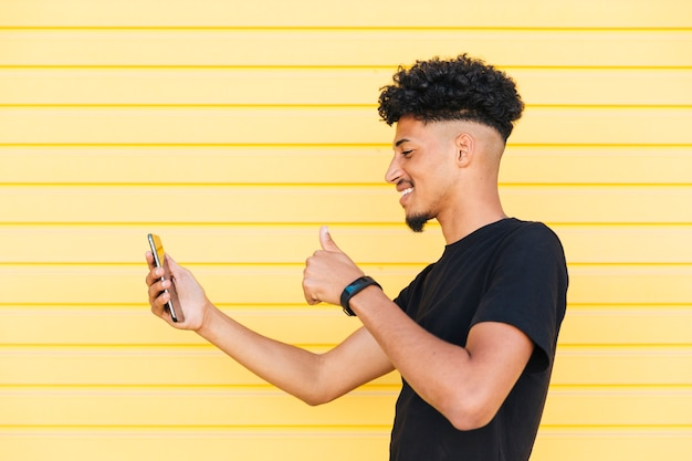 Cheerful ethnic male taking selfie with thumb up Free Photo