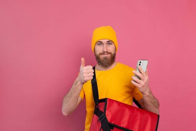 핑크에 가방 캐주얼 보류 전화와 쾌활 한 유럽 배달 남자 무료 사진