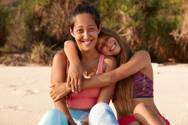 陽気なヨーロッパの女性は彼女の仲間を抱きしめ、一緒にスポーツトレーニングをし、ビーチに座っています 無料写真
