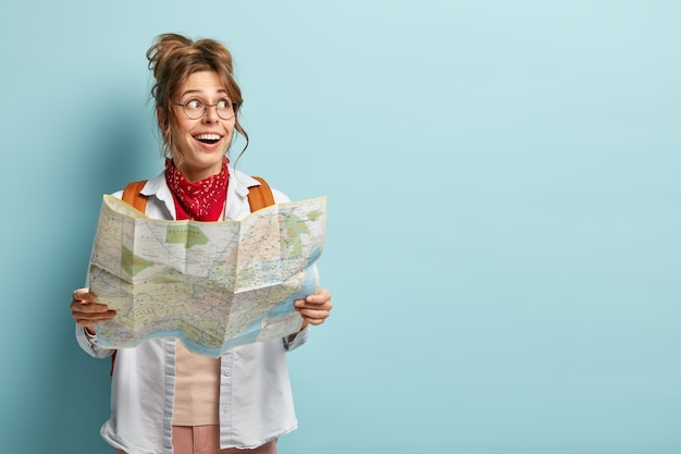 Cheerful european woman has interesting trip, looks aside, holds map, checks route or location, travels in tourist city Free Photo