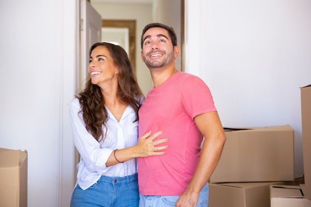 Cheerful excited couple moving into new house, standing among carton box, hugging and looking around Free Photo