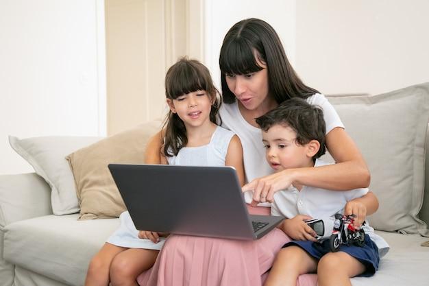 幸せな子供を抱き締めるとノートパソコンの画面を指して陽気な興奮しているママ。家族が自宅のソファに座って映画を見ています。 無料写真