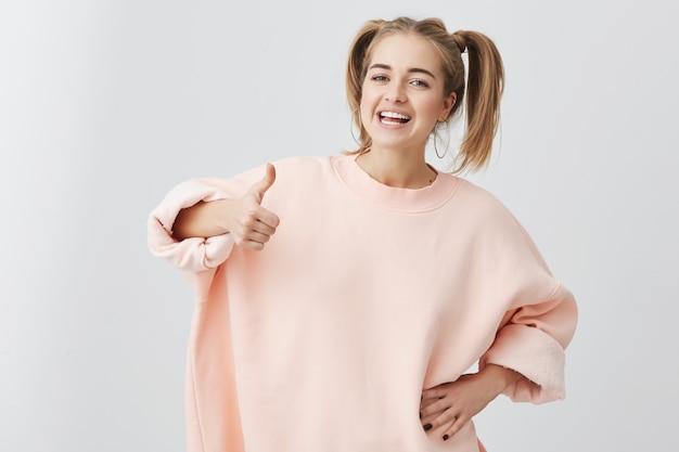 Веселая взволнованная молодая кавказская самка с двумя хвостиками, в розовом свитере, показывает жестом ok и улыбается, демонстрируя свои белые зубы, наслаждаясь своей беззаботной жизнью. все просто отлично! Бесплатные Фотографии
