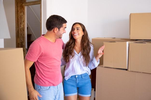 カートンボックスの間に立って、新しいアパートを抱き締めて話し合う陽気な家族のカップル 無料写真