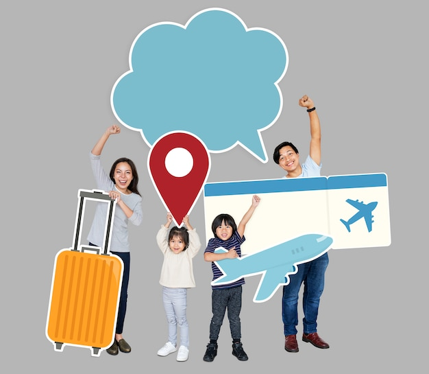 Cheerful family holding travel icons and ticket Premium Photo