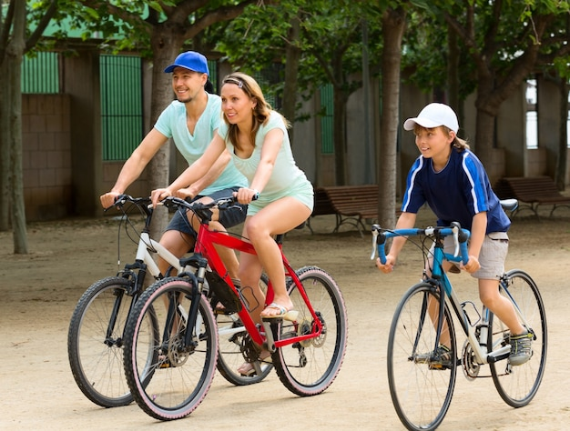 Cheerful family of three cycling on city road Free Photo