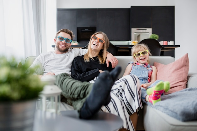 Cheerful family watching film on couch Premium Photo