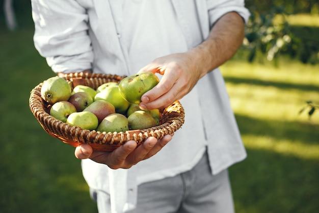 庭に有機リンゴを持つ陽気な農家。籐のかごの中の緑色の果物。 無料写真