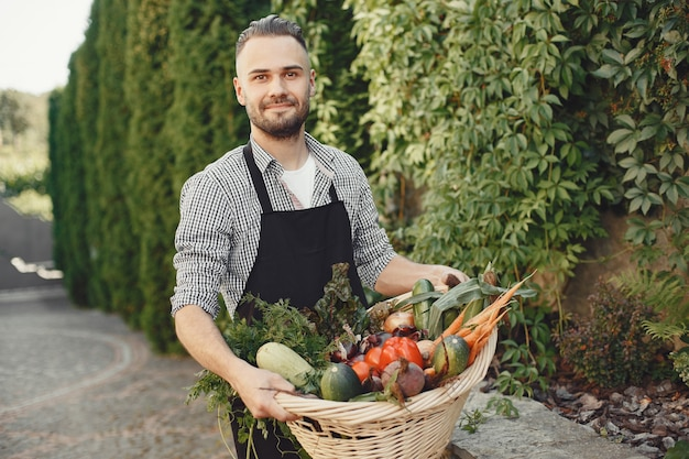 Cheerful farmer with organic vegetables in garden. mixed organic vegetable in wicker basket. Free Photo