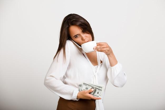 Веселая модница, пью кофе, держу деньги и разговариваю по телефону Бесплатные Фотографии