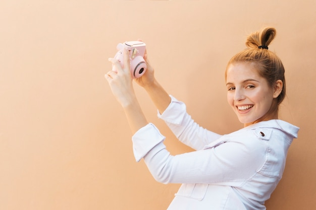 Cheerful fashionable young woman taking selfie on pink instant camera against brown background Free Photo