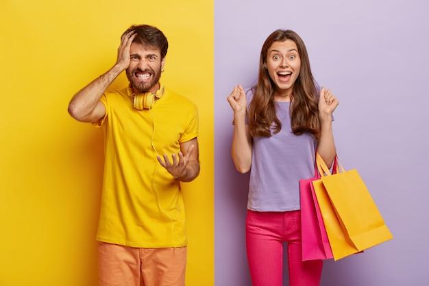 Веселая самочка несет разноцветные сумки для покупок, радуется новой покупке, сжимает кулаки от радости, раздраженный муж злится на жену-шопоголик, жестикулирует с раздражением Бесплатные Фотографии