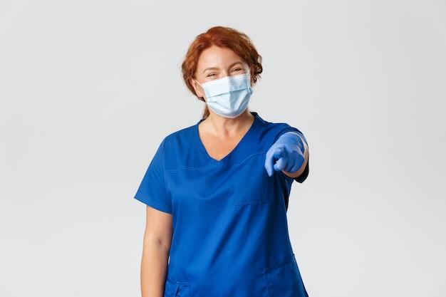 Allegro dottoressa, medico rossa o infermiera in scrub, maschera per il viso e guanti sorridendo amichevole e indicando la fotocamera Foto Gratuite