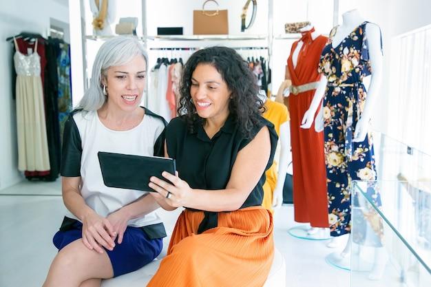 Allegri amici femminili seduti insieme e utilizzando tablet, discutendo di vestiti e acquisti nel negozio di moda. copia spazio. il consumismo o il concetto di acquisto Foto Gratuite
