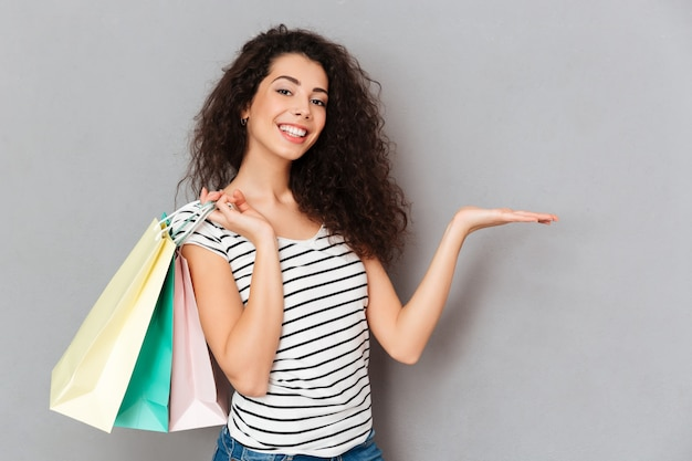 Cheerful female shopaholic being excited with all purchases and packs after shopping demonstrating product on her palm copy space Free Photo