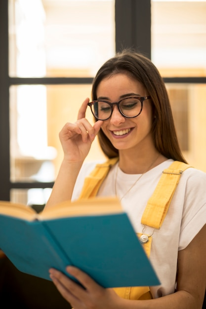 Cheerful female student reading book in eyeglasses Free Photo