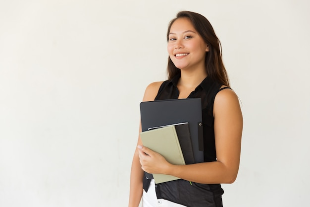 Cheerful female student with folder and textbooks Free Photo