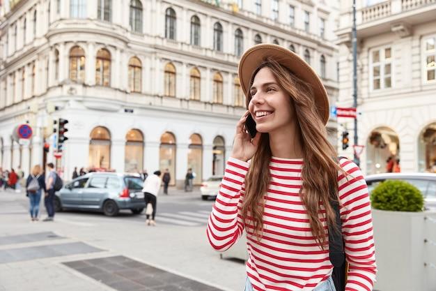 陽気な女性の放浪者は街を散歩し、コミュニケーションを楽しみ、現代のスマートフォンを耳の近くに保ち、脇に集中します 無料写真