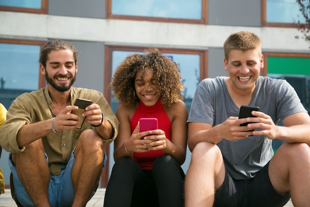 Cheerful focused multiethnic students using their phones Free Photo