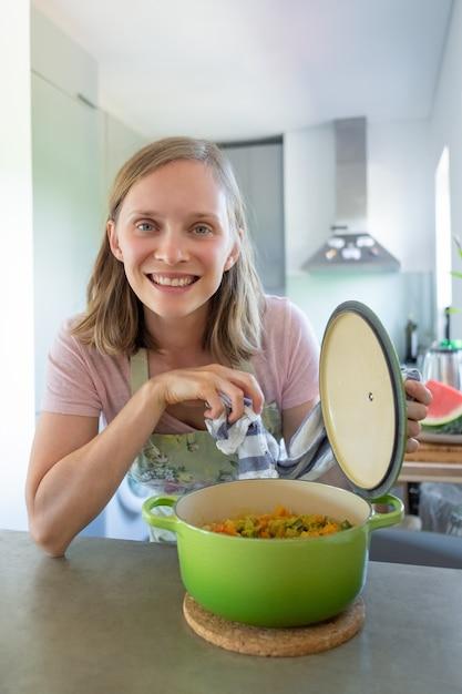 陽気な料理のブロガーが野菜の食事で鍋を開き、テーブルにもたれて、カメラにポーズをとって、笑顔で。垂直ショット。家庭料理のコンセプト 無料写真