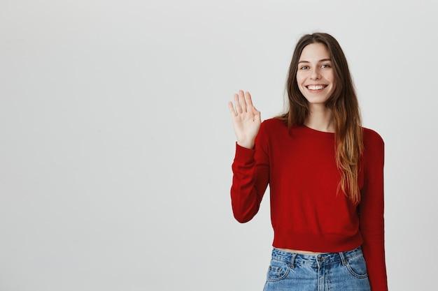 Mano d'ondeggiamento della donna attraente amichevole allegra, dicendo ciao Foto Gratuite