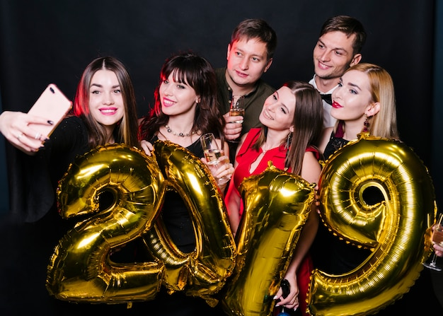 Cheerful friends doing selfie with balloons number 2019 Free Photo