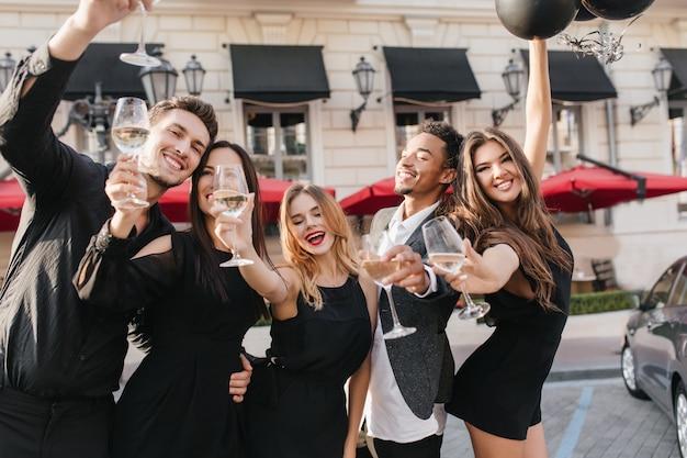 Веселые друзья пьют шампанское на вечеринке на открытом воздухе Бесплатные Фотографии