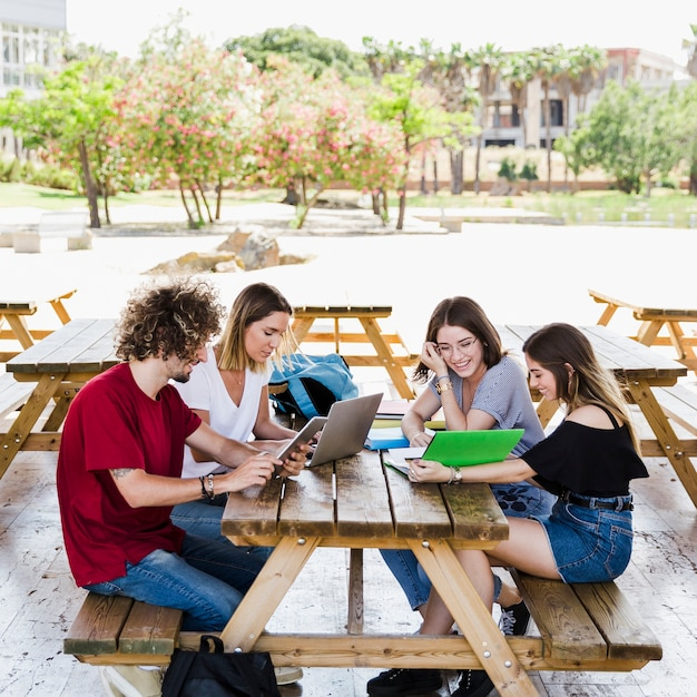 Cheerful friends studying at table Free Photo
