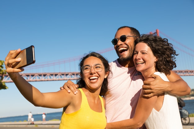 Cheerful  friends taking selfie with smartphone Free Photo