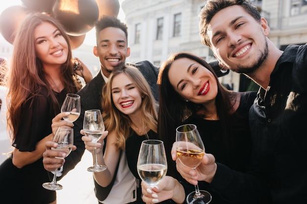 お祝いの間に写真を作る笑顔で陽気な友達 無料写真