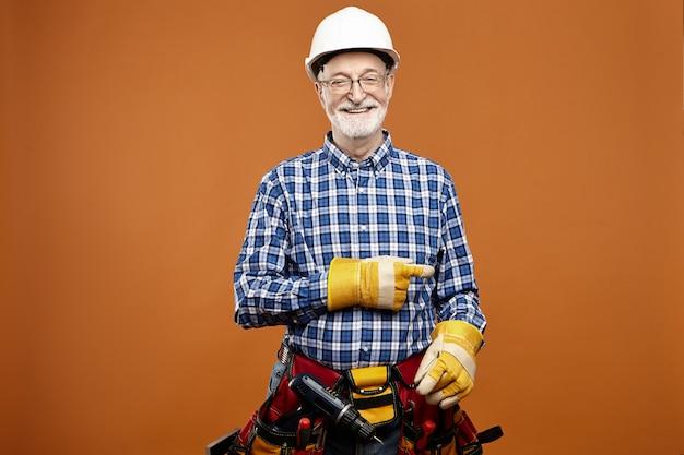 腰の周りに作業機器を運ぶ人差し指を指している陽気な白人の年配の男性の大工。保護手袋とツールベルトでポーズをとって笑顔の年配のひげを生やした電気技師 無料写真