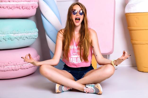 蓮華座で床に座っている陽気な面白い女の子。ピンクの一重項とショートパンツで笑顔としかめっ面の顔を作る幸せなブロンドの女性。瞑想と狂気の感情、喜び 無料写真