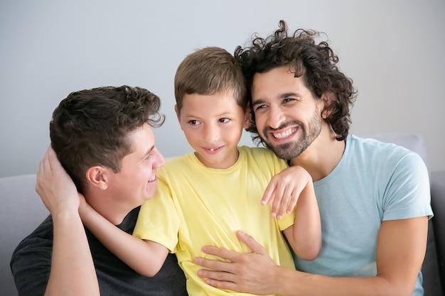 쾌활한 게이 아버지와 아들이 함께 소파에 앉아 서로 포옹. 전면보기. 행복한 가족과 부모 개념 무료 사진