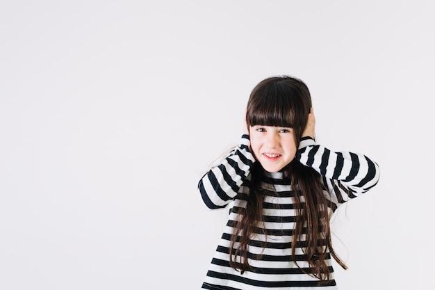 Cheerful girl covering ears Free Photo