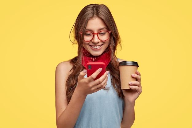 La ragazza allegra fa una pausa caffè, si rallegra dell'acquisto di nuovi gadget, legge la notifica sul cellulare rosso, aggiorna l'app preferita, digita il messaggio e sorride sullo schermo, indossa gli occhiali, isolato su un muro giallo Foto Gratuite