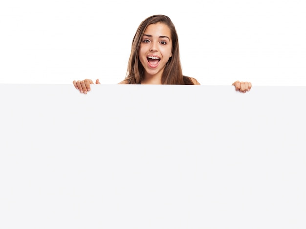 Cheerful girl holding a blank poster Free Photo