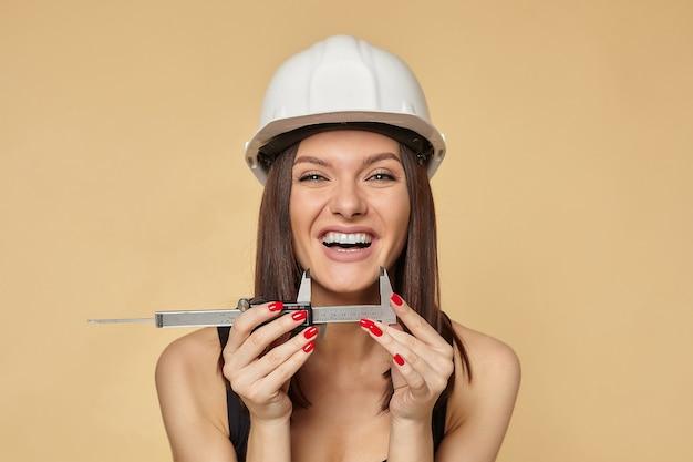 Веселая девушка в белом шлеме держит штангенциркуль и меряет улыбку Premium Фотографии