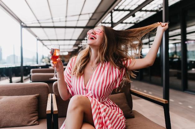 세련 된 스트라이프 드레스 카페에서 재미와 칵테일 마시는 명랑 소녀. 레스토랑에서 포즈를 취하는 동안 그녀의 머리를 가지고 노는 금발 백인 여자를 웃 고있다. 무료 사진