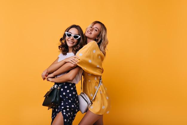友人との余暇を楽しんでいるヴィンテージの白いサングラスの陽気な女の子。黄色を抱きしめる華やかな身なりのよい女性。 無料写真