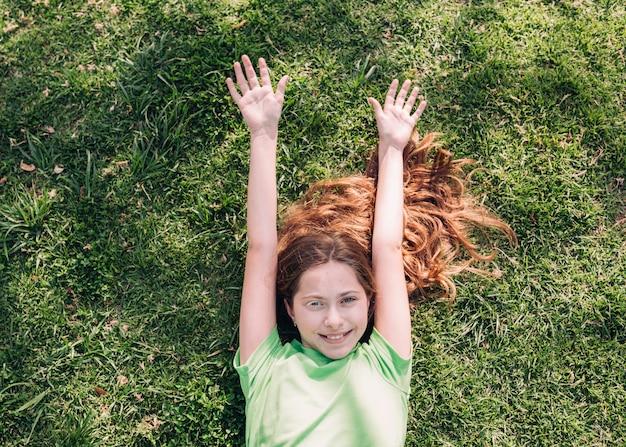 Cheerful girl lying on grass in sunlight Free Photo