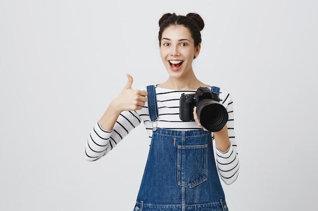 親指を立てて、モデルの良い仕事を賞賛し、褒め言葉を作る陽気な女の子の写真家 無料写真