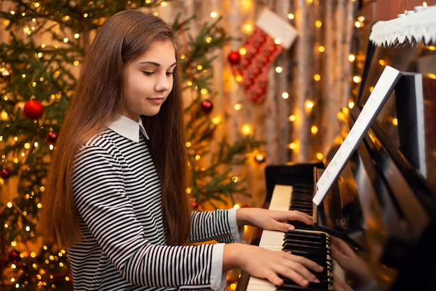 Cheerful girl playing the piano with decorated christmas tree on the background Premium Photo