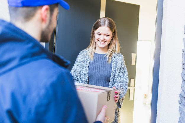 Cheerful girl receiving delivered box Free Photo
