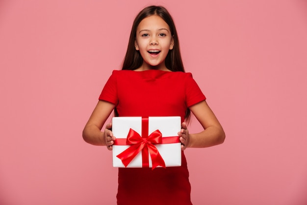 Cheerful girl showing gift and smiling isolated over pink Free Photo