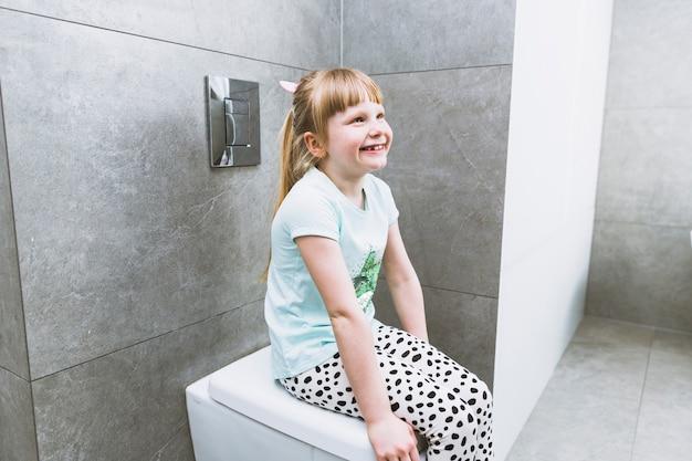 Cheerful girl sitting on toilet Free Photo