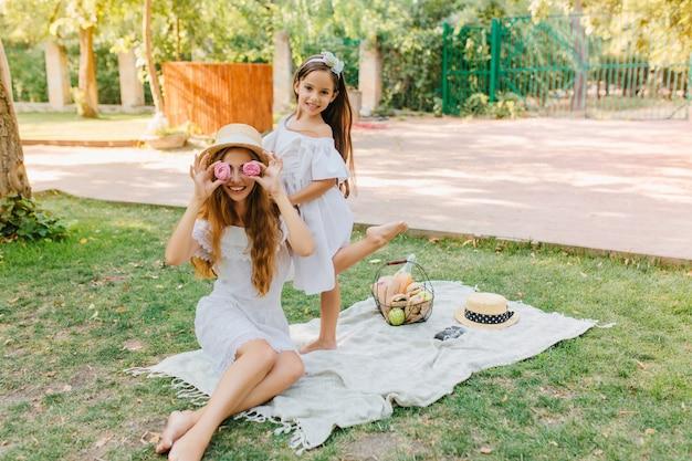 彼女の面白い母親がクッキーで浮気しながら片足で立っている陽気な女の子。休暇中に娘とピクニックを楽しんで冗談の長い髪の女性の屋外の肖像画。 無料写真