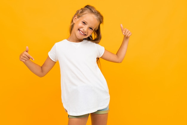 Cheerful girl in a white t-shirt smiles against a yellow Premium Photo