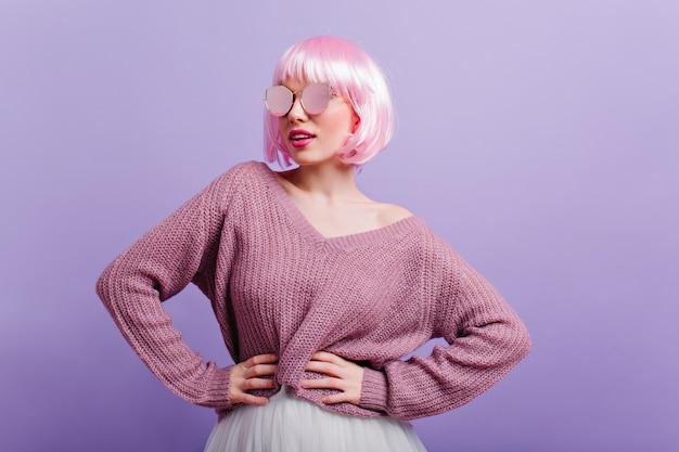 Жизнерадостная девушка с розовыми прямыми волосами, стоя в позе уверенно и улыбаясь. симпатичная европейская дама в свитере и блестящих очках танцует во время фотосессии. Бесплатные Фотографии